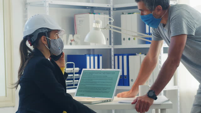 teamwork in a new office setup. co-working on a business project during covid-19 pandemic. brainstorming. two colleagues wearing protective face masks at work to flatten the curve - engineer stock videos & royalty-free footage