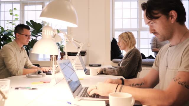 stockvideo's en b-roll-footage met teamwork in moderne coworking-ruimte-multi-etnische groep van professionals die samenwerken - freelancer