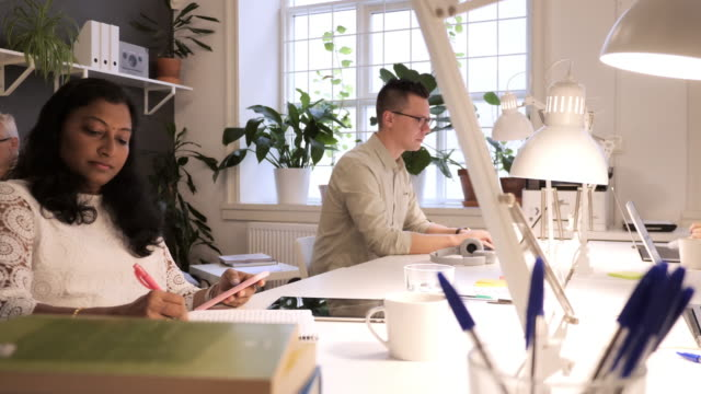 teamwork in modern coworking space - multi ethnic group of professionals working together - scandinavia stock videos & royalty-free footage