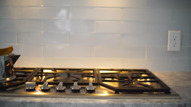 vidéos et rushes de théière simplement sur la cuisinière à gaz, vapeur va de plafond - carrelage