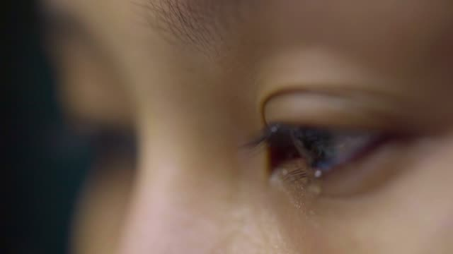 close up: tear comes out of an eye and streaks down the cheek. sad abused female with brown eyes crying , asian model. - tristezza video stock e b–roll