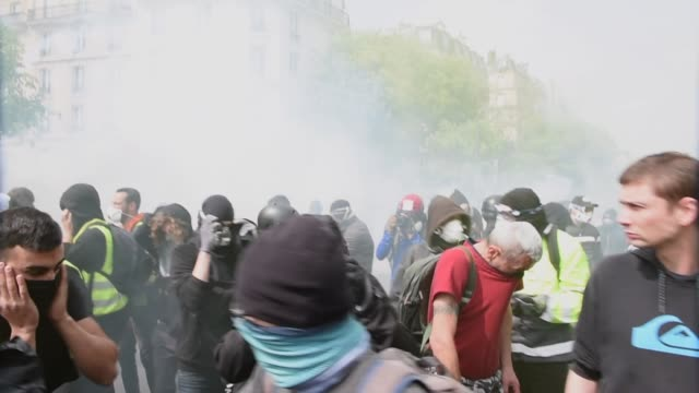 vídeos de stock e filmes b-roll de tear gas and grenades rain down on a group of protesters and black-blocks during the may 1 parade clashes in paris, in paris, france, on may 1, 2019. - dia do trabalhador