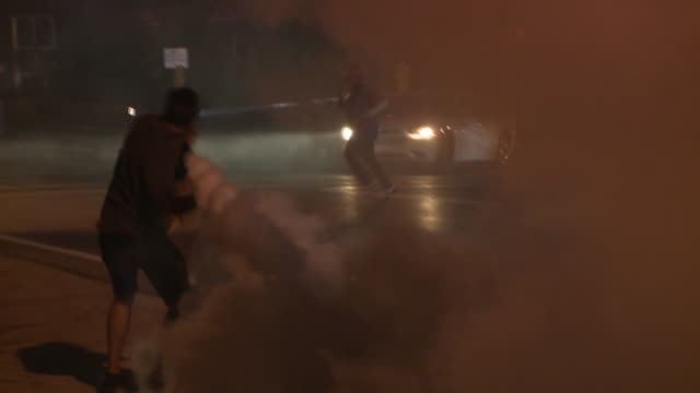 ktvi tear gas fills the street and a young man throws a tear gas canister on august 18 2014 in ferguson missouri protests and riots broke out in the... - missouri stock videos & royalty-free footage