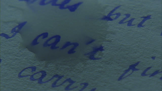 A tear smudges the cursive writing on a page.