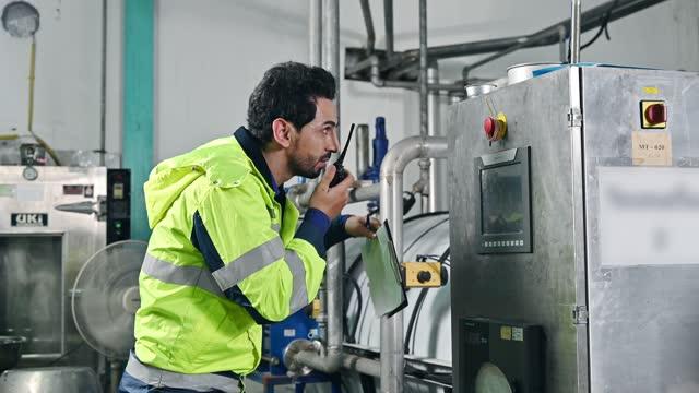 飲料製造工場で異常な運転状況を観察するための変圧器電源制御パネルの無線通信チェック及び書き込み報告状態を有する技術エンジニア - 分析機器点の映像素材/bロール
