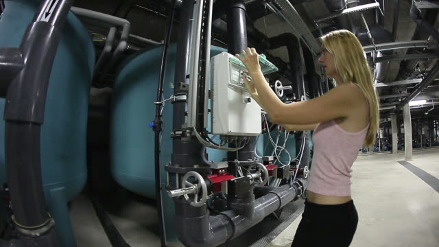 stockvideo's en b-roll-footage met technical expert woman in plant underground checking a control panel - regelkamer