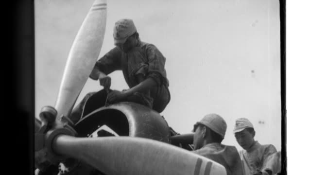 Technical school leaders wear white coveralls as they observe mechanic apprentices assemble the rudder assembly of a Type 96 land attack bomber and...