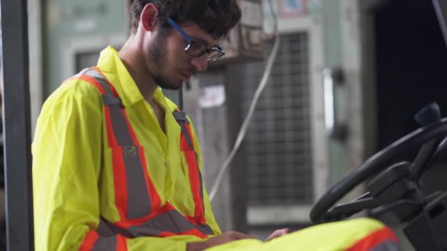 vidéos et rushes de travailleur technique vérifiant le smartphone pendant le temps de pause à l'usine - apprenti