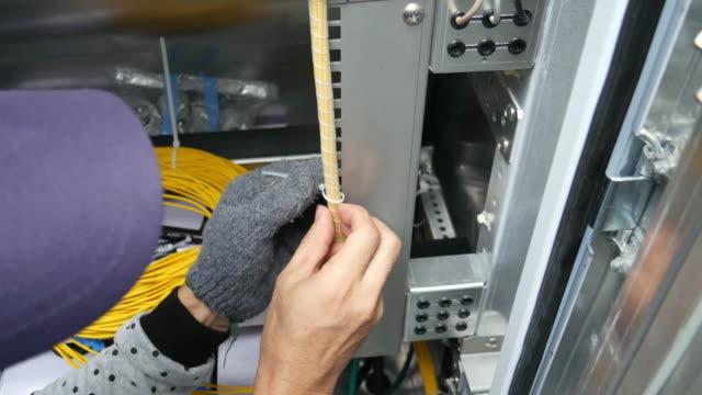 vídeos de stock, filmes e b-roll de técnico trabalhador está fazendo reorganizar cabo de fibra óptica em telecomunication equipamentos de balcão - fibra