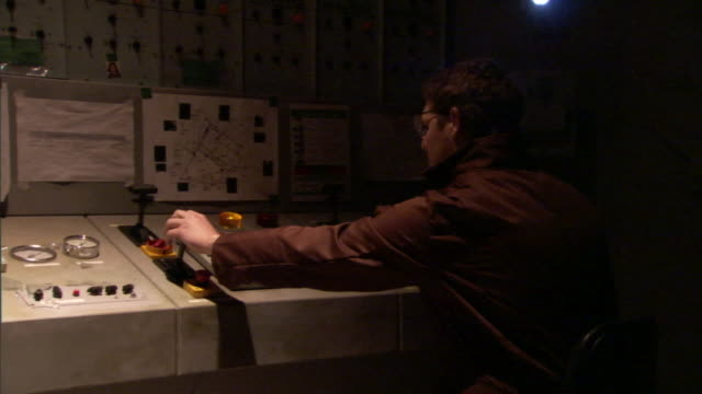 a technician adjusts controls on a flashing control panel when it explodes and sends sparks flying. - control panel stock videos & royalty-free footage