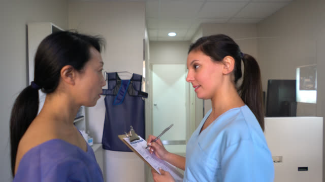 technician asking routine questions to patient before a mammography - examining stock videos and b-roll footage