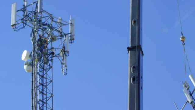 a technician assembles a cell phone tower as a crane hoists parts on a clear, sunny day - wireless technology stock videos & royalty-free footage