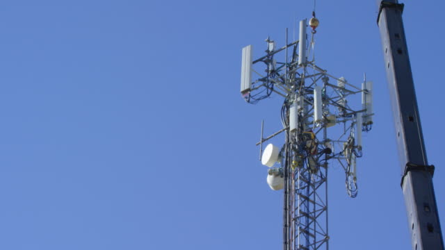 a technician assembles a new cell phone tower on a clear, sunny day - technician stock videos & royalty-free footage