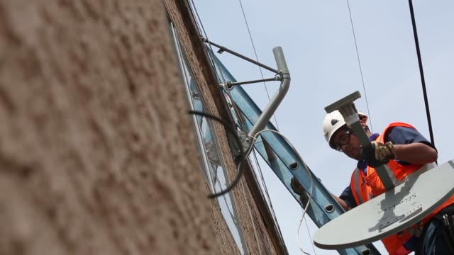 A DIRECTV technician assembles a new satellite TV dish while performing an installation for a tenant at a apartment building in Lynwood California US...