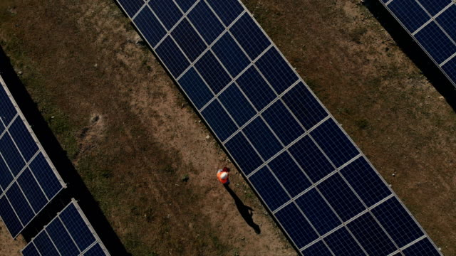 technician at solar power station aerial shot - quality control stock videos & royalty-free footage