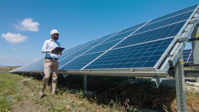 vídeos de stock, filmes e b-roll de técnico na usina de energia solar - geração de combustível e energia