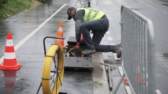 technician at work on a street when installing cable for broadband internet optical fiber on june 12, 2020 in villeneuve la garenne, france. - cable stock videos & royalty-free footage