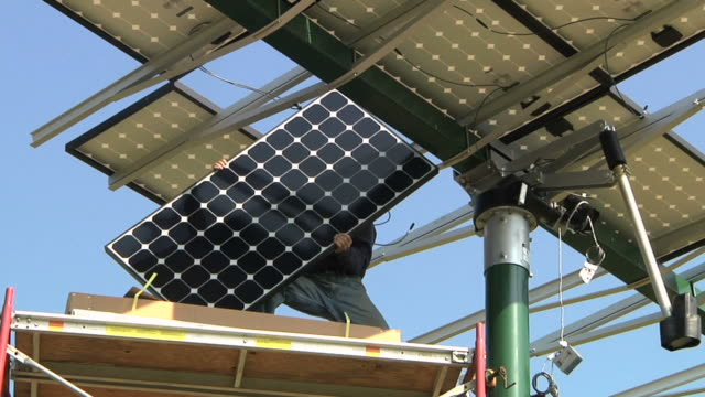 ms pan technician attaching panel to photovoltaic array / grass lake, michigan, usa      - techniker stock-videos und b-roll-filmmaterial
