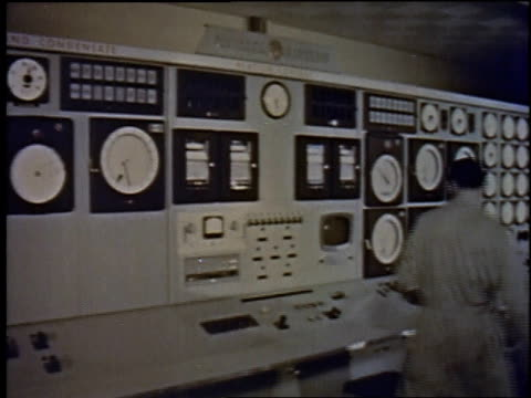 1957 MONTAGE technician checking equipment, dials on reactor / New York City, New York, United States