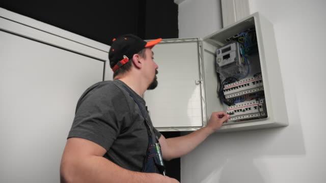 vidéos et rushes de technicien cochant la boîte de fusible, ralenti - ligne à haute tension