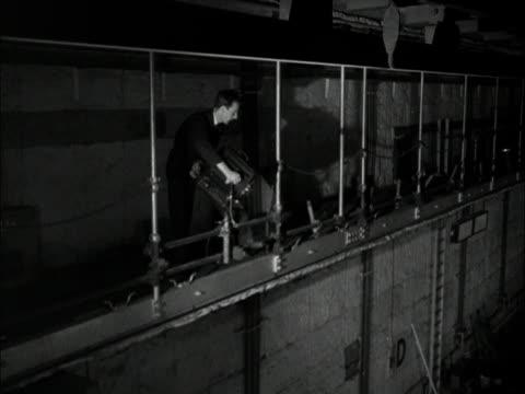 vídeos y material grabado en eventos de stock de a technician checks a spotlight in the new bbc children's hour studio at lime grove 1950 - bbc