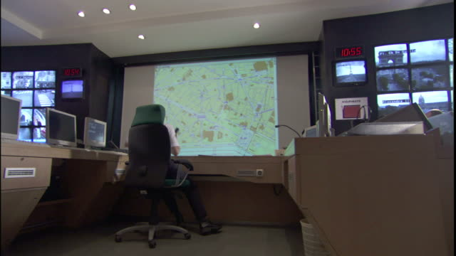 a technician controls surveillance monitors and maps in a large control room. - control room stock videos & royalty-free footage