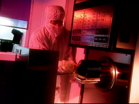 technician dressed in clean suit moving rack of silicon wafers in laboratory / westchester, new york - wafer stock videos and b-roll footage