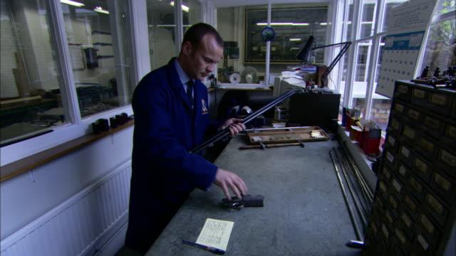 vídeos de stock e filmes b-roll de a technician grabs a shotgun and a handgun from a bench. - banco assento