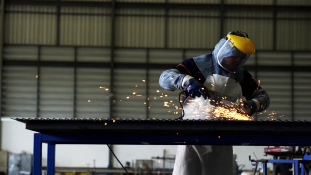 techniker schleifen metall mit einem elektrischen schleifer in einer uniform und tragende sicherheitsausrüstung. - kunsthandwerkliches erzeugnis stock-videos und b-roll-filmmaterial