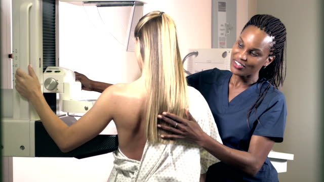 technician helping woman get mammogram - semi dress stock videos & royalty-free footage