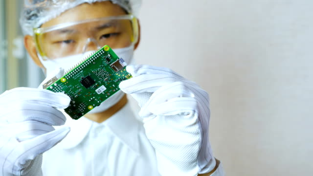 technician holding and investigating micro controller board in clean room - wafer stock videos and b-roll footage