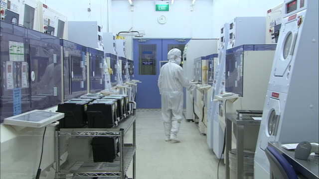 MS, Technician in white suite entering computer clean room through slide door, rear view, Singapore