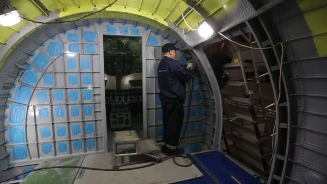 A technician inspects the computer displays and control systems on the flight deck of a Sukhoi Superjet 100 aircraft at the Sukhoi Civil Aircraft Co...