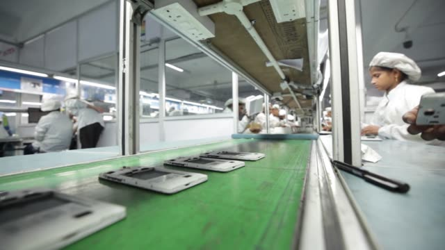 a technician inspects the sound output and microphone input of a smartphone on the production line inside the intex technologies india ltd plant in... - production line stock videos & royalty-free footage