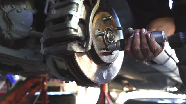 tecnico che installa il freno a disco sull'auto - elica parte di macchina video stock e b–roll