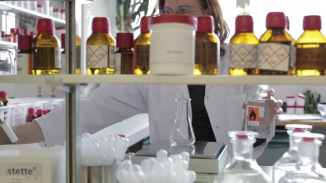 a technician is seen working at a computer beyond rows of sample bottles stored on shelves in the flavor research laboratory at givaudan sa... - scented stock videos & royalty-free footage