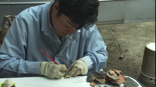 a technician marks a pottery shard. - archaeologist stock videos & royalty-free footage
