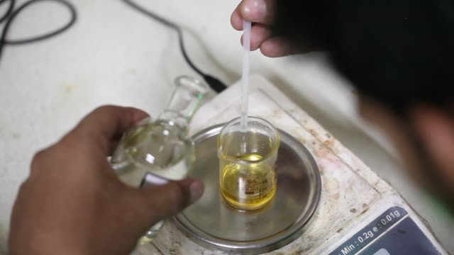 a technician mixes oils in the fragrance laboratory at the fragrance flavour development centre in kannauj uttar pradesh india on tuesday june 2 a... - uttar pradesh stock videos and b-roll footage