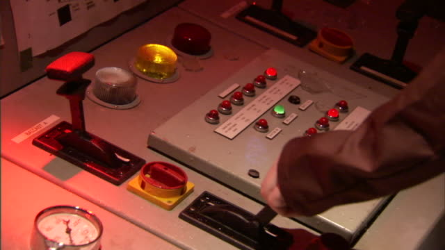 a technician moves a throttle on a control panel where a red warning light flashes. - control panel stock videos & royalty-free footage
