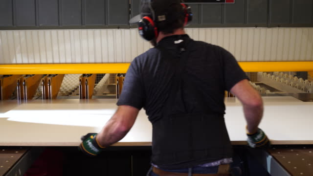 vídeos de stock e filmes b-roll de technician operates computerized wood cutting equipment - protetor de ouvido
