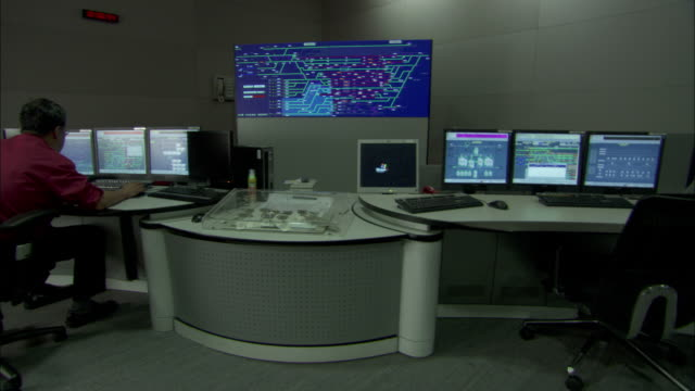 A technician operates computers and monitors data in a control room.