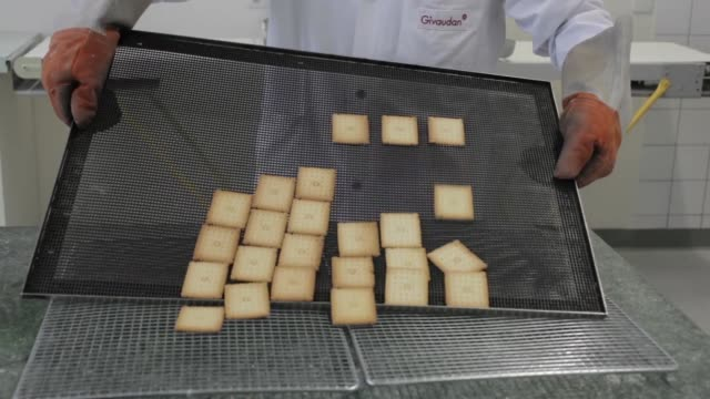 a technician places and removes a sample of freshly baked butter biscuits from an oven ahead of testing at givaudan sa flavor research laboratory... - scented stock videos & royalty-free footage