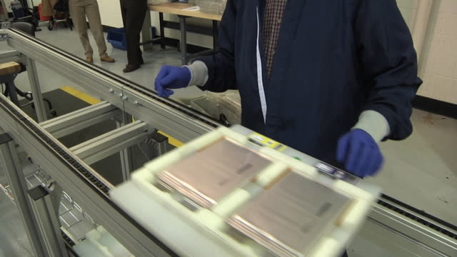 MS Technician placing lithium ion cells used in automobile batteries on transport in prototype lab / Troy, Michigan, USA