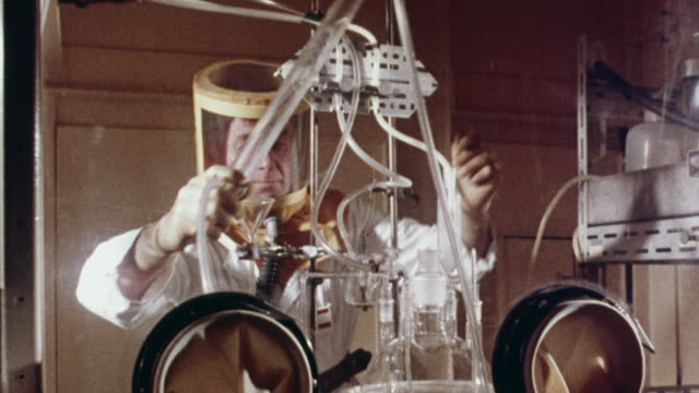 vídeos y material grabado en eventos de stock de 1957 ms technician replacing water condenser with air condenser using glove boxes / united kingdom - 1957