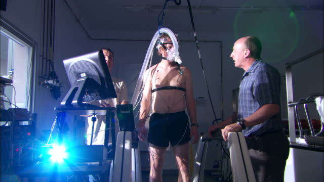 a technician speaks to an athlete on a treadmill in a heat chamber. - treadmill stock videos & royalty-free footage