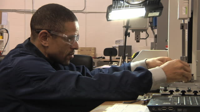 CU ZI PAN Technician testing weld strength in lithium ion battery used to power electric automobiles / Troy, Michigan, USA