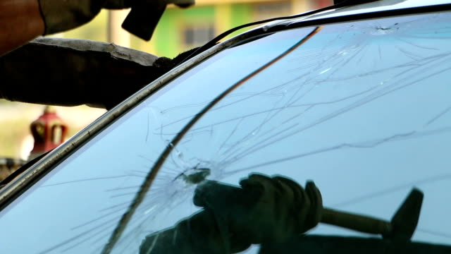 Technician use hammer for Broken car windshield. Selective focus