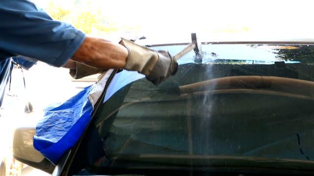 技術者は、壊れた車のフロント ガラスにハンマーを使用します。選択と集中 - 残骸点の映像素材/bロール