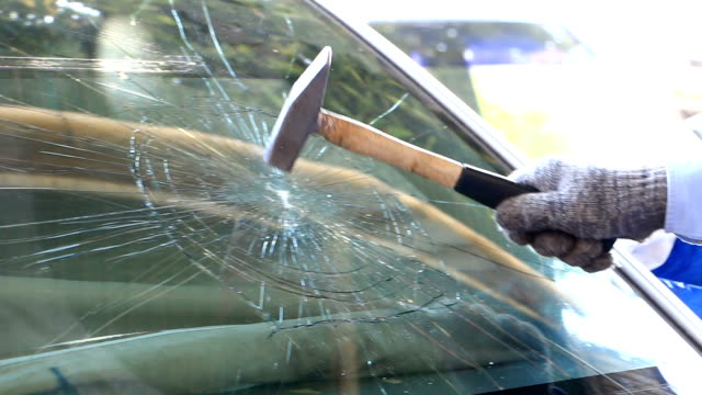 technician use hammer for broken car windshield. selective focus - safety stock videos & royalty-free footage
