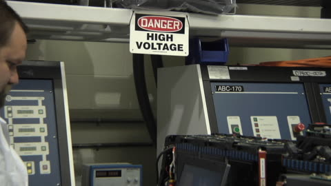 cu zo technician using computer while testing prototype lithium ion battery used to power electric automobile in high voltage area / troy, michigan, usa - high voltage sign stock videos & royalty-free footage